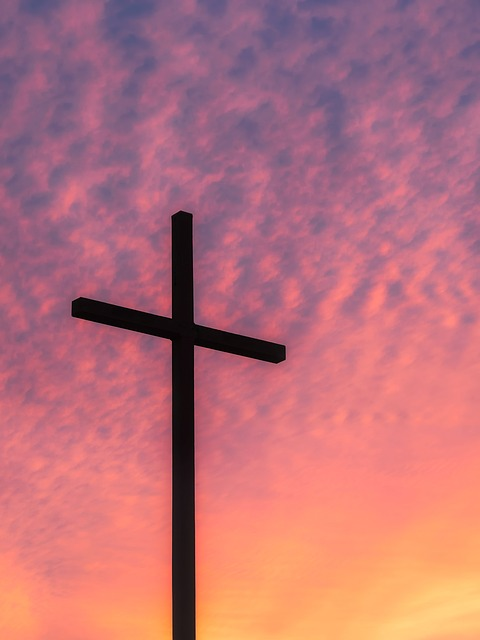 Cross in sunrise pink and purple clouds
